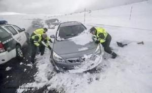 Guardia Civil trabajando para mover un coche atrapado en la nieve